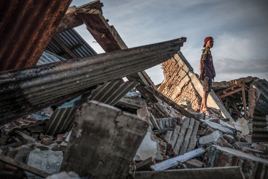 A resident stands on the ruins of a building that was destroyed by the earthquake. A deadly earthquake measuring 7.5 magnitude and the tsunami wave caused by it has destroyed the city of Palu and much of the area in Central Sulawesi. According to the officials, death toll from devastating quake and tsunami rises to 1,480, around 800 people in hospitals are seriously injured and some 62,000 people have been displaced in 24 camps around the region.