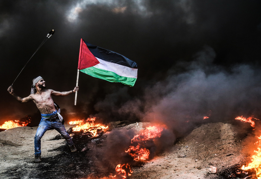 Palestinian protester seen holding a flag while using a slingshot to hurl stones during the clashes following a demonstration near the border with Israel.