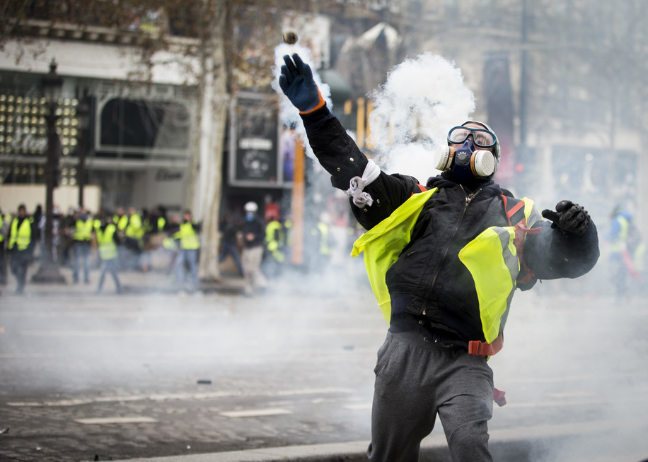 A protester seen throwing back a teargas canister toward police officers (not pictured) near the Arc De Triomphe during a 'Yellow Vest' protest in Paris. Without any political affiliation, the 'Yellow Vest' movement rallies in various cities in France this saturday against taxes and rising fuel prices.