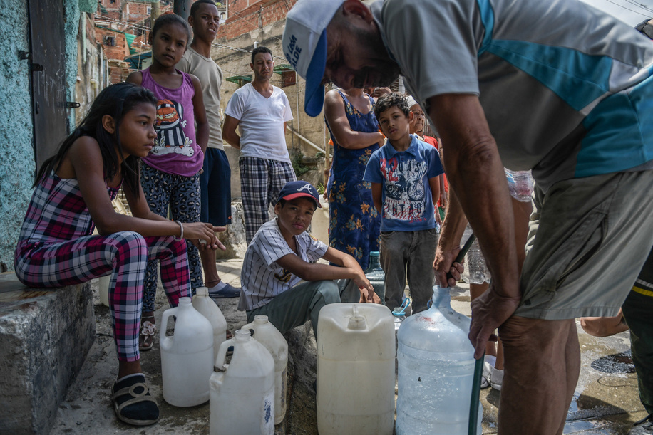 People seen with plastic bottles in a queue to get water during a water shortage. Lack of water affected the standard of living in Venezuela, the situation intensified after a national blackout that lasted 3 days. The services have been severely affected. In Petare, one of the largest poor sectors in Latin America, they have gone for more than 30 days without water.
