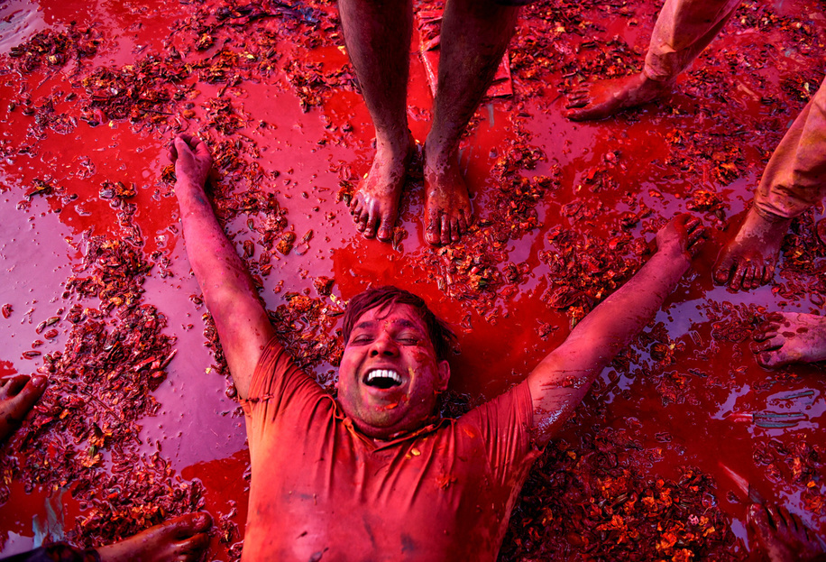 A Hindu devotee seen lying on the ground of Radharani Temple after completion of Holi celebration at Nandgaon. Holi Festival of India is one of the biggest Holi celebration in India as many Tourists and devotees gather to observe this colourful programme.