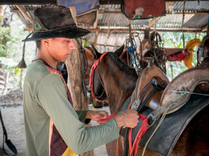 Cowboy seen saddling a horse at the El Paraíso finca. Colombian cowboys taking care of the cows in the region of Casanare, eastern Colombia, between the Andes, the Orinoco River and the border with Venezuela. These are Plains and pastures with wide rivers and marshes, a region of big biodiversity. But nowadays, it is in danger because of climate change.