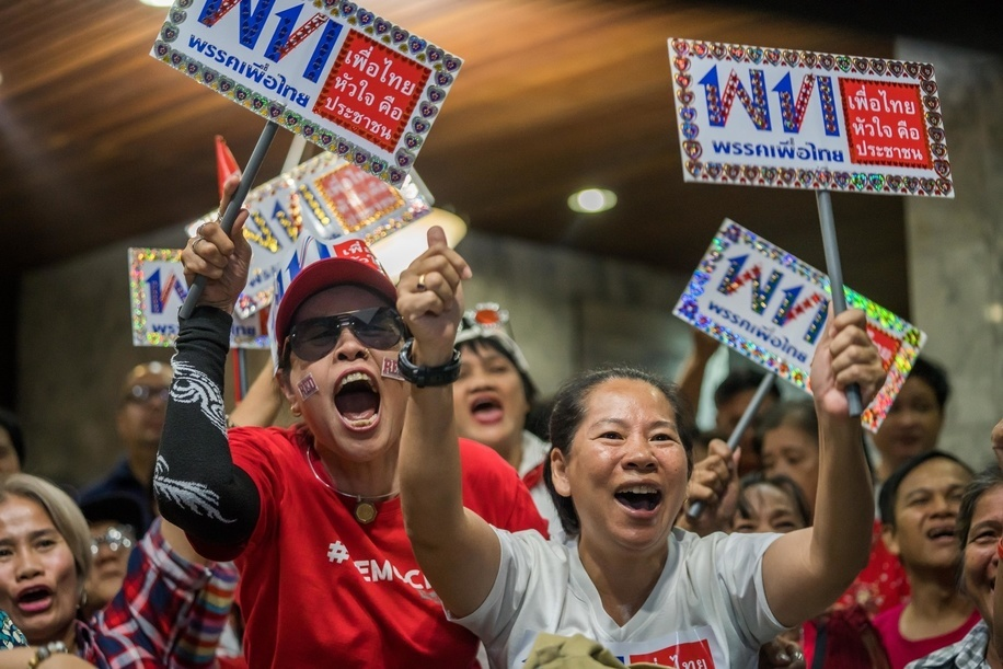 Supporters of the Pheu Thai Party celebrate as one of their candidates wins a seat as they watch the live polling results on TV in the Pheu Thai Party headquarters. The people of thailand is waiting for the final election result as the polling station has closed and cotes are being counted.