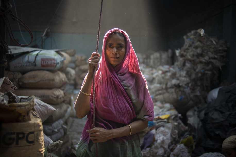A woman seen looking directly at the camera while working at a plastic recycling factory. Most of the factories do not maintain any proper working conditions for any of its labourers.