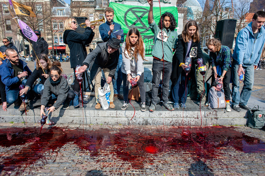 Activists are seen pouring fake blood during the protest. Extinction Rebellion (XR) is an international movement that uses non-violent civil disobedience to achieve radical change in order to minimize the risk of human extinction and ecological collapse. From Monday 15 April, Extinction Rebellion is taking action on the streets of cities all over the world. In The Hague, the 'International Rebellion XR Netherlands' declared its own full-scale rebellion to demand decisive action from governments on climate change and ecological collapse. Also the Blood of our Children', a symbolic act where buckets of fake blood were poured on the street right next to the government offices to show the politicians that every second is more blood on their hands.
