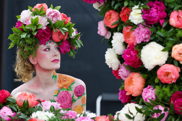 A model seen wearing a floral display hat with body art posing  for photographers during the Chelsea flower show. The Royal Horticultural Society Chelsea Flower Show is an annual garden show over five days in the grounds of the Royal Hospital Chelsea in West London. The show is open to the public from 21 May until 25 May 2019.