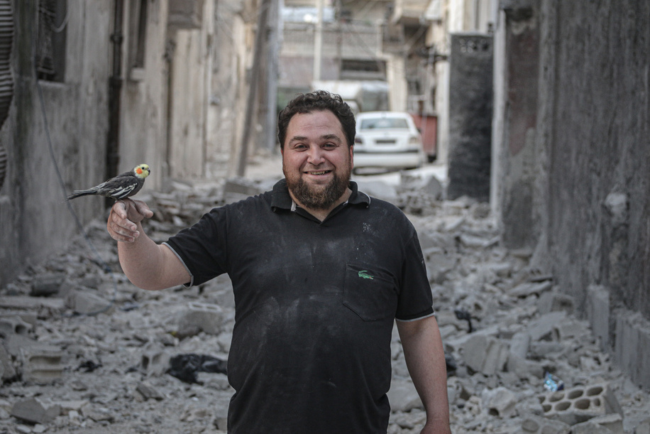 One of the survivors seen carrying a bird after his house was completely destroyed. Aftermath of the Russian planes and Bashar al-Assad planes shelling on buildings with no mercy on civilians or animals in Ariha, Syria.