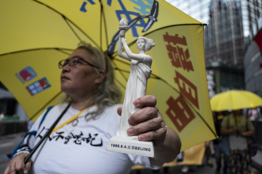 A protester seen holding a yellow umbrella and a Goddess of Democracy statue, during the demonstration. Pro-democracy participants attend the protest commemorating the 30th anniversary of the 1989 Tiananmen Square crackdown also known as the June Fourth incident or Six Four (6 4) where thousands of demonstrators were massacred by the military that was advancing towards Tiananmen Square.