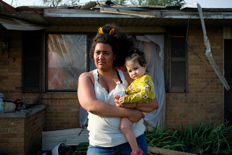 Breann holds her baby in front of their damaged house from the previous nights tornado that struck the area. At least 1 person is dead and 12 injured from the storms that hit western Ohio.