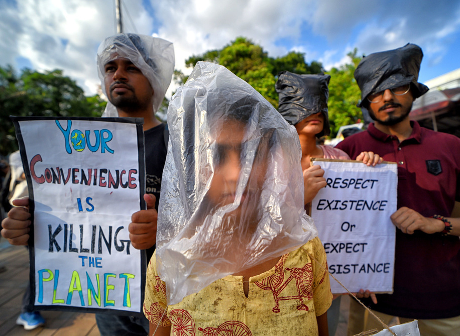 An Activist from Friday for Future group with their faces wrapped with Plastic bags while holding placards on Plastic Threat to create an awareness programme in Kolkata. Plastic pollution in world rapidly destroying natural environment & making high impact on Climate.