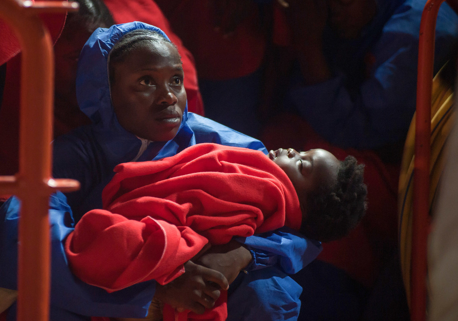 A migrant woman are seen holding a baby migrant on a rescue vessel as she waits to disembark after their arrival at the Port of Malaga. Spain's Maritime Rescue service rescued a total of 174 migrants (of them, 35 women and 7 children) aboard three dinghies crossing the Alboran Sea and brought them to Malaga harbour, where they were assisted by the Spanish Red Cross.