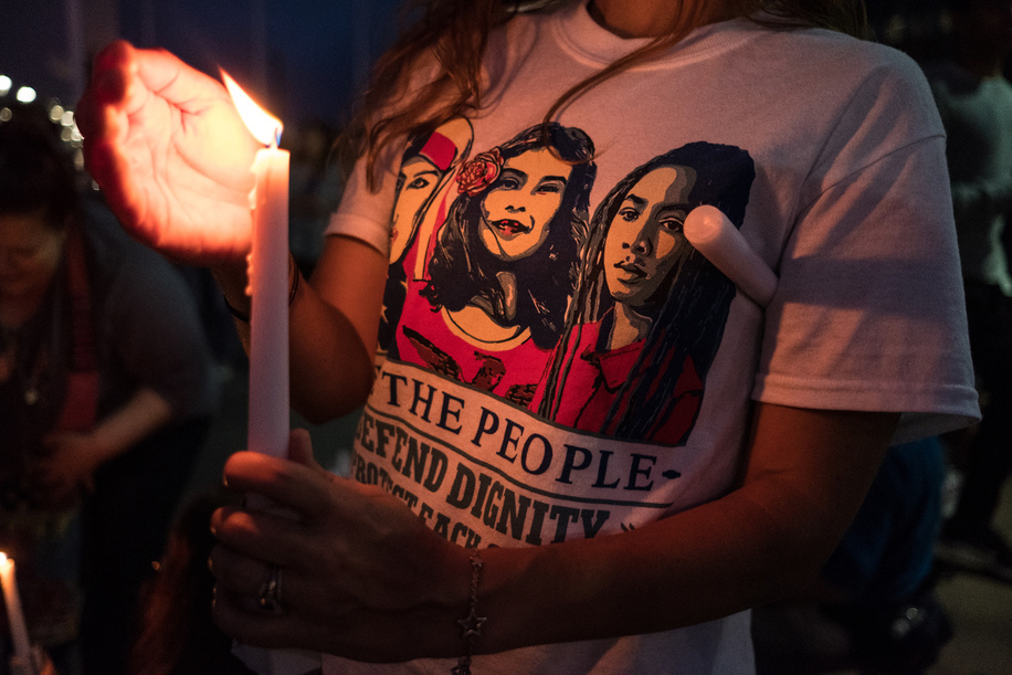 Woman with a lit candle during the protest. Over one thousand people gathered in San Ysidro near the US Mexico border to protest against treatment of asylum seekers in US detention centers. 24 immigrants have died in ICE custody during Trumps administration.