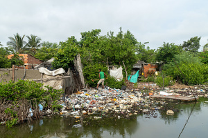 A man collects plastic waste from a river at the La Boquilla during a clean-up session in Cartagena. Fundacion CoraJeM works in educating and creating opportunities for the people in need. Teaching them culture and values, it allows them to build up a better future and live with more dignity.
