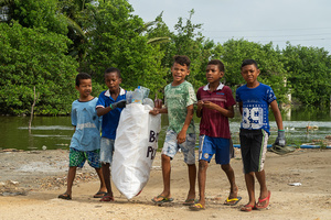 Children carry a sack of plastic waste at the La Boquilla during a clean-up session in Cartagena. Fundacion CoraJeM works in educating and creating opportunities for the people in need. Teaching them culture and values, it allows them to build up a better future and live with more dignity.