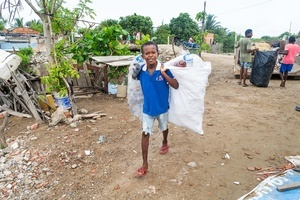 A young boy carries a sack of plastic waste at the La Boquilla during a clean-up session in Cartagena. Fundacion CoraJeM works in educating and creating opportunities for the people in need. Teaching them culture and values, it allows them to build up a better future and live with more dignity.