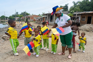 Young kids hold flags at the La Boquilla during a clean-up session in Cartagena. Fundacion CoraJeM works in educating and creating opportunities for the people in need. Teaching them culture and values, it allows them to build up a better future and live with more dignity.