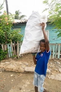 A boy holds a sack of plastic waste at the La Boquilla during a clean-up session in Cartagena. Fundacion CoraJeM works in educating and creating opportunities for the people in need. Teaching them culture and values, it allows them to build up a better future and live with more dignity.