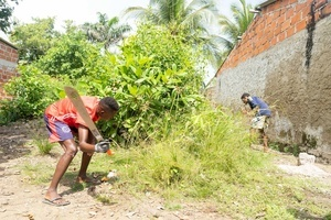 Young men clearing shrubs at the La Boquilla during a clean-up session in Cartagena. Fundacion CoraJeM works in educating and creating opportunities for the people in need. Teaching them culture and values, it allows them to build up a better future and live with more dignity.