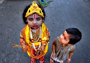 A little kid seen dressed up as Lord Krishna while her sister admires her as they attend the Janmastami Festival in  Kolkata. Janmastami is an annual Hindu festival that celebrates the birth of Krishna - incarnation of Vishnu as per Hindu mythology.