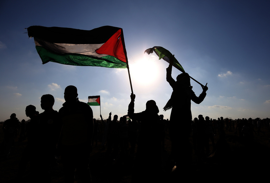 Palestinian Protesters hold Palestinian flags during an anti-Israel demonstration at the Israel-Gaza border fence in the southern Gaza Strip.