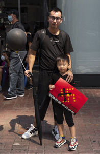 A father and his son wearing black outfit in Causeway Bay rally. Thousands of anti-china protesters marched and clashed with police in Hong Kong as the party celebrates its 70th year of rule.