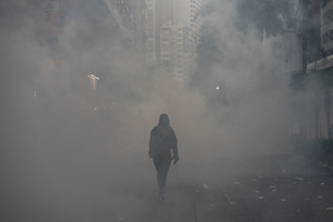 A protester is being surrounded by tear gas smoke in Wan Chai, Hong Kong during the clashes. Thousands of anti-china protesters marched and clashed with police in Hong Kong as the party celebrates its 70th year of rule.