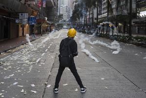 A protester stands defiant despite tear gas canisters being fired by the police during the clashes. Thousands of anti-china protesters marched and clashed with police in Hong Kong as the party celebrates its 70th year of rule.