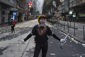 A protester encourages his comrades during the clashes with police. Thousands of anti-china protesters marched and clashed with police in Hong Kong as the party celebrates its 70th year of rule.
