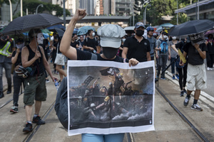 A protester raises her hand while chanting anti-government slogans during the demonstration. Thousands of anti-china protesters marched and clashed with police in Hong Kong as the party celebrates its 70th year of rule.