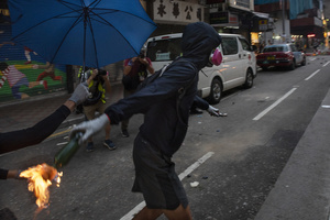 A protester throws at the police a cocktail molotov on fire during the clashes. Thousands of anti-china protesters marched and clashed with police in Hong Kong as the party celebrates its 70th year of rule.