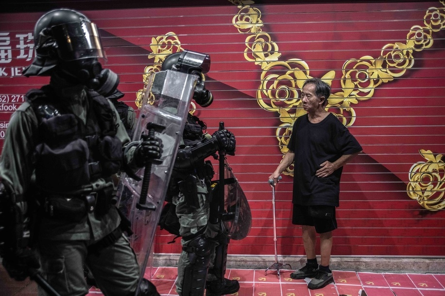 A man observes a group of policemen in Causeway Bay during the demonstration. Protesters attend a Global Anti-Totalitarianism March in Hong Kong - Demonstrations continue in Hong Kong marking one of the worst days of violence in 4 months of unrest.