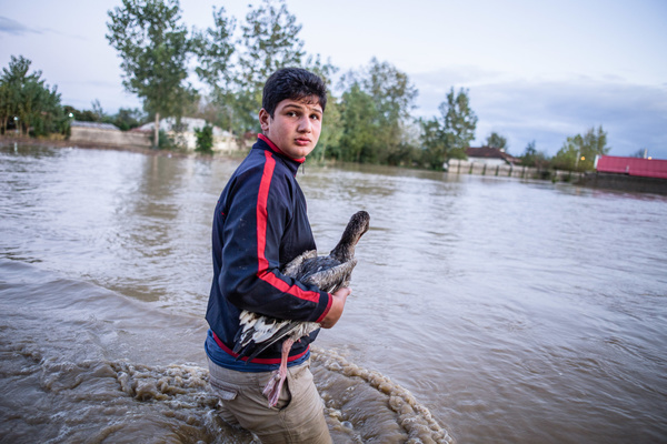 A boy walks through a flooded road.Around 200 people were affected by heavy rains that caused a flood on Gilan province. Several bridges collapsed and some roads were blocked. The flood has caused one death and itís the second consecutive year in the village of Sheikh Mahala, disrupting normal life.