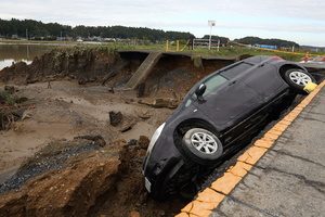 A car falls off a road destroyed by floods. The death toll rises to 48, two days after Typhoon Hagibis passed through Japan while 15 are still missing and more than 100 injured as thousands of troops are deployed on rescue missions across the country.