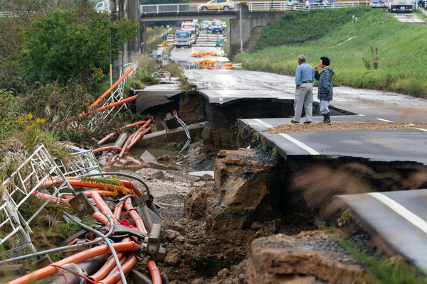 Local residents walk on a collapsed road following the Typhoon Hagibis. The death toll rises to 48, two days after Typhoon Hagibis passed through Japan while 15 are still missing and more than 100 injured as thousands of troops are deployed on rescue missions across the country.
