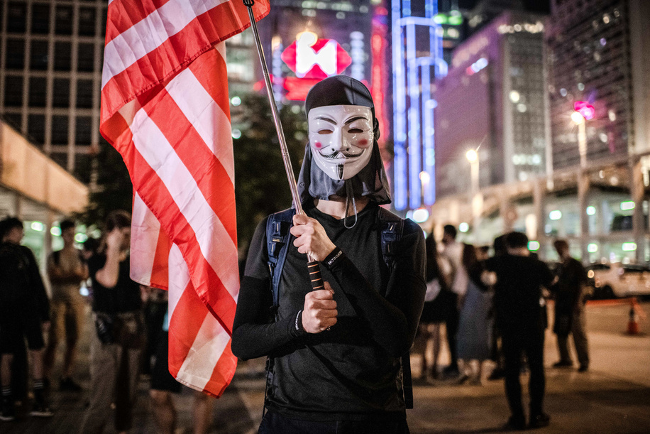 A masked protester holds an American flag during the demonstration.Hong Kong people call for international SOS and humanity aid at Edinburgh Place, Central in a demonstration against the Anti-mask Law. Hong Kong's chief executive Carrie Lam invoked the use of the Emergency Regulations Ordinance (ERO) allowing the government to ban use of masks in public gatherings.