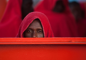 A sub-Saharan migrant covered with a red blanket looks on in a rescue vessel on arrival at the Port of Malaga. A total of 61 migrants were rescued from a dinghy at the Mediterranean Sea by Spain's Maritime Rescue Service and brought them to Malaga harbor where they were assisted by the Spanish Red Cross.