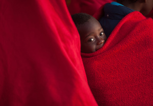 A sub-Saharan migrant child looks on while smiling in a rescue vessel on arrival at the Port of Malaga. A total of 61 migrants were rescued from a dinghy at the Mediterranean Sea by Spain's Maritime Rescue Service and brought them to Malaga harbor where they were assisted by the Spanish Red Cross.