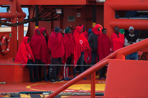 Sub-Saharan migrants covered with red blankets in a rescue vessel on arrival at the Port of Malaga. A total of 61 migrants were rescued from a dinghy at the Mediterranean Sea by Spain's Maritime Rescue Service and brought them to Malaga harbor where they were assisted by the Spanish Red Cross.