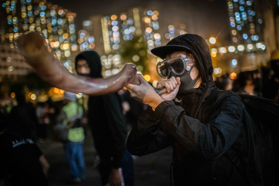 A protester blows a horn outside mourning place in Tseung Kwan O during the demonstrations.Hong Kong mourns death of student Chow Tsz-lok, a 22 years old University student who died from cardiac arrest in the morning of Friday, 8th of November. Chow Tsz-lok fell from a car park amid chaotic confrontations between Hong Kong riot police and protesters, suffering a severe head injury. Thousands took the streets to mark his passing on. Candlelight vigils were held at the car parking where the incident took place.