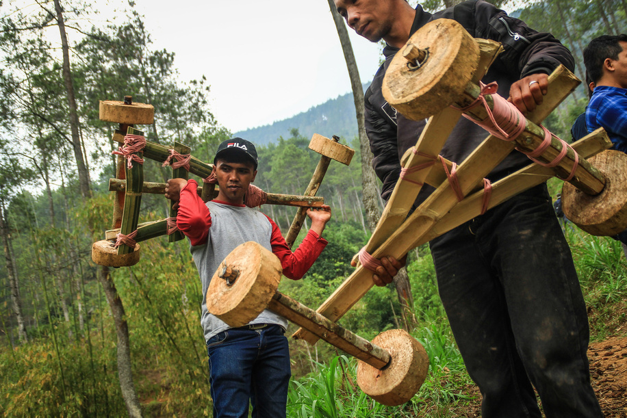 Residents moves up the hill while carrying bamboo cars in Batu Lonceng Village, Lembang. The traditional game is a hereditary tradition held during the growing season holidays as well as entertainment to villagers.