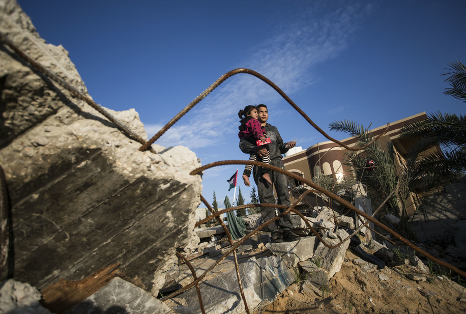 A Palestinian man carrying his sister at the site of their destroyed house. The Abu Umrah family that consists of 19 individuals lost their five-storied house after an Israeli raid on Gaza on November 13, 2019.