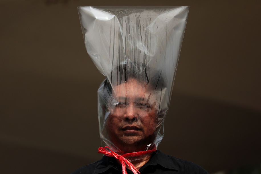 A protester wears a plastic bag on his head during the rally. Environmental activists rally to demand rights to clean air, near the Thai Government House in Bangkok, Thailand, as the country struggles to contain worsening air pollution.