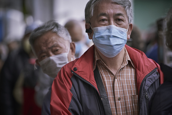 An old man wearing a surgical mask during the giveaway. Giveaway of surgical masks drew hundreds of elderly queuing up for hours under the fear of the deadly corona virus in Hong Kong.