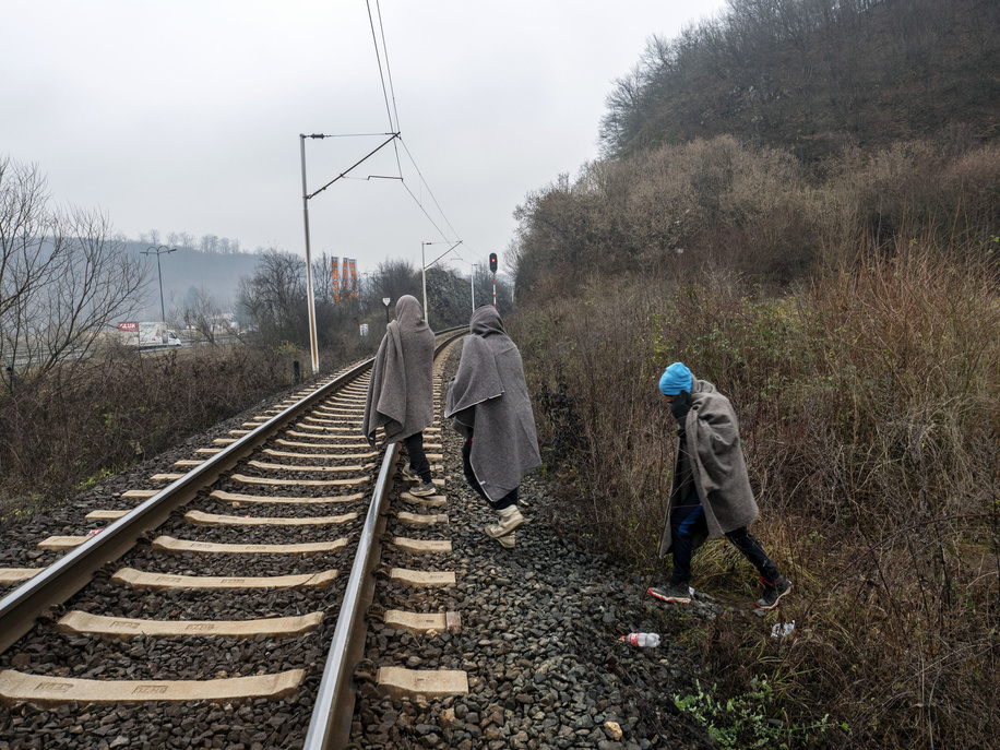Three migrants walking through the railway lines close to Sarajevo. In Bosnia and Herzegovina around 8,000 refugees and migrants try to find a way how to cross the border to Croatia and get further to the Western European countries. Some of them live in overcrowded refugee camps, some of them squat in abandoned buildings or simply sleep in the streets. Many of them report that if they are caught on the border by Croatian police, they are beaten, their cash money, smart phones and valuables are stolen, jackets and shoes are burnt and they are beaten by the border guards.