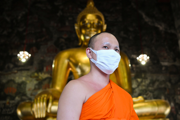 BANGKOK, THAILAND - MARCH 17, 2020: A Thai Buddhist monk wear a face mask to protect himself against the coronavirus (Covid-19). For most people, the new coronavirus causes only mild or moderate symptoms, such as fever and cough. For others, especially older adults and people with existing health problems, it can cause more severe illness, which can lead to death. 30 new cases of the Covid-19 has been confirmed by the Public Health Ministry of Thailand today, which now raised the total number of infections to 177 since the beginning of the outbreak.