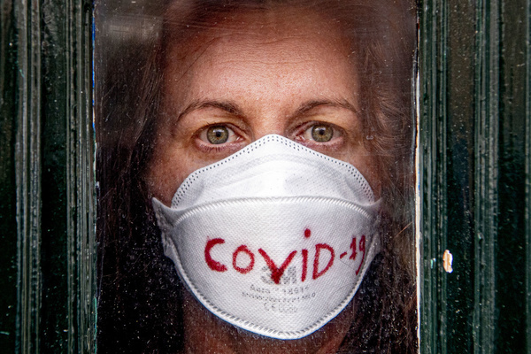 In this photo illustration a covid-19 coronavirus patient poses for photo looking out from her front door at her home as she is being quarantined. A 40 years old lady who doesn't want to be named has been tested and confirmed positive to the Covid-19 coronavirus after returning to the Netherlands from her trip in Italy 2 weeks ago has been ordered to stay home to quarantine herself by the local health authority to prevent her from spreading the virus.