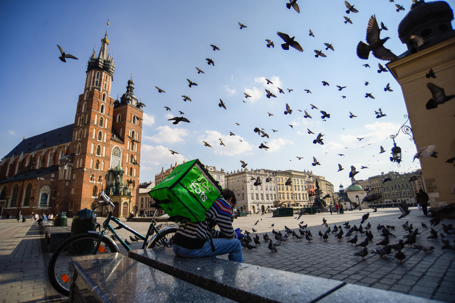 KRAKOW, POLAND - MARCH 20, 2020: An Uber eats delivery man takes a rest in an almost empty Main Square during the state of emergency. Poland has a total of 367 confirmed cases of coronavirus (COVID-19) and five people dead. The ruling government has declared a state of emergency and closure of its borders, schools, bar, restaurants among other institutions.