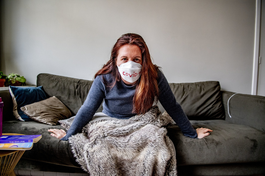 In this photo illustration a covid-19 coronavirus patient rest on her sofa pose for photo as she is being quarantined at her home. A 40 years old lady who doesn't want to be named has been tested and confirmed positive to the Covid-19 coronavirus after returning to the Netherlands from her trip in Italy 2 weeks ago has been ordered to stay home to quarantine herself by the local health authority to prevent her from spreading the virus.