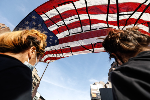 Demonstrators hold an American flag as they march through the streets during the protest. Protests continue against police brutality and racial injustice in New York City.