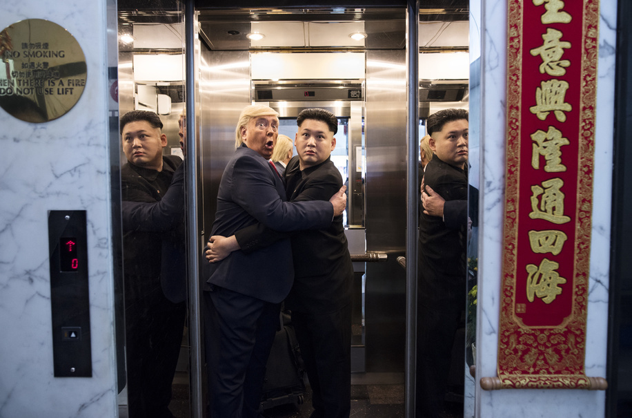 Donald Trump and Kim Jong-un impersonators jokingly hug each other in a elevator.